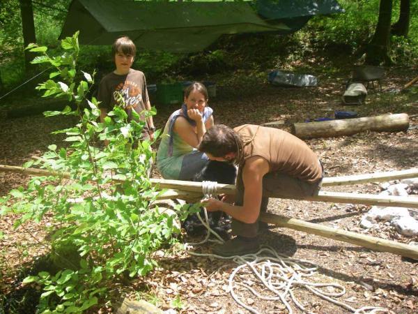 Sebastian bindet den Dreifuß - Astrid und Luca schaun zu